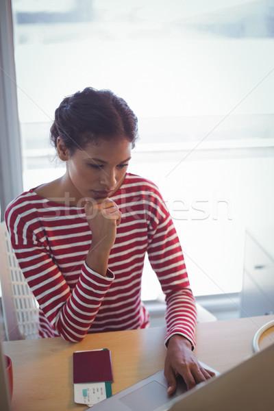 Serious businesswoman using laptop in office Stock photo © wavebreak_media