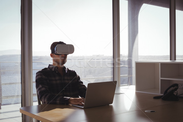 Businessman using virtual reality headset and laptop in office Stock photo © wavebreak_media