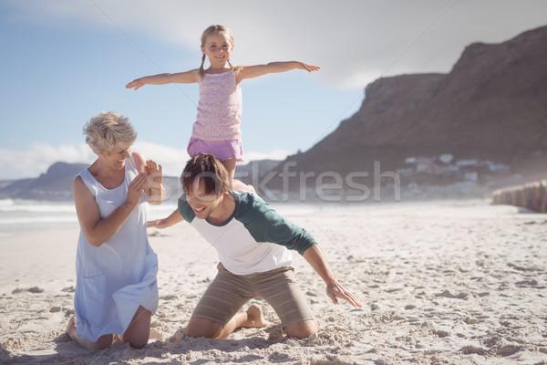 Happy girl kneeling on father back at beach Stock photo © wavebreak_media