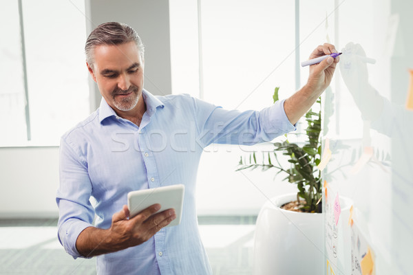 Attentive executive using digital tablet while writing on whiteboard Stock photo © wavebreak_media