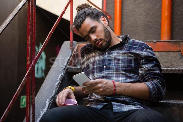 Man using mobile phone while having drink on staircase Stock photo © wavebreak_media