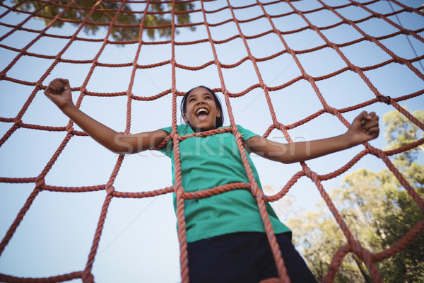 Happy girl cheering while climbing a net during obstacle course Stock photo © wavebreak_media