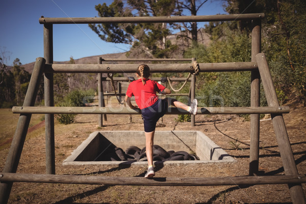 Rear view of girl climbing outdoor equipment during obstacle course Stock photo © wavebreak_media
