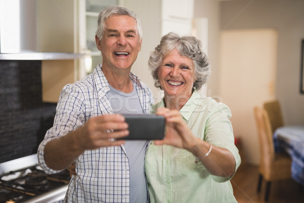 Happy senior couple taking selfie in kitchen Stock photo © wavebreak_media