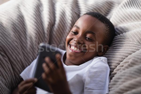 Mały chłopca gry telefonu kanapie salon Zdjęcia stock © wavebreak_media