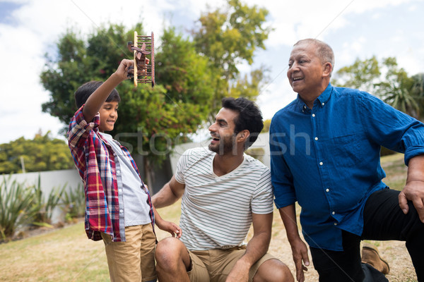 Boy showing toy airplane to father crouching by senior man Stock photo © wavebreak_media
