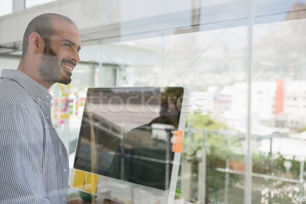 Smiling designer looking away seen through glass Stock photo © wavebreak_media