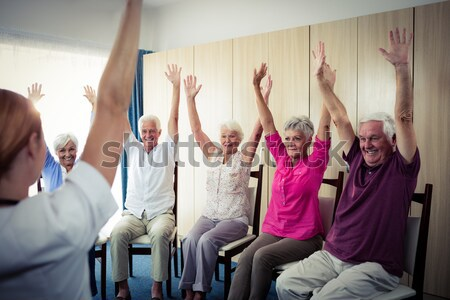 Cheerful seniors and female doctor sitting with raised hands Stock photo © wavebreak_media