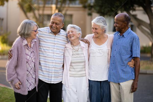 Smiling senior friends standing with arms around Stock photo © wavebreak_media