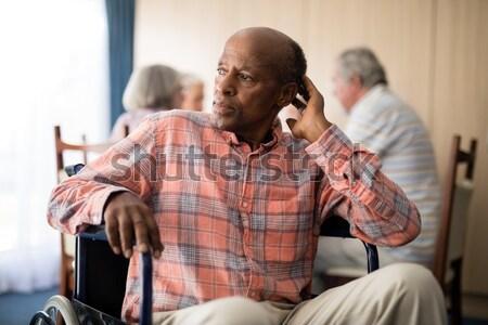улыбаясь старший человека глядя мобильного телефона сидят Сток-фото © wavebreak_media