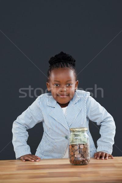 Ritratto donna sorridente monete vetro jar grigio Foto d'archivio © wavebreak_media