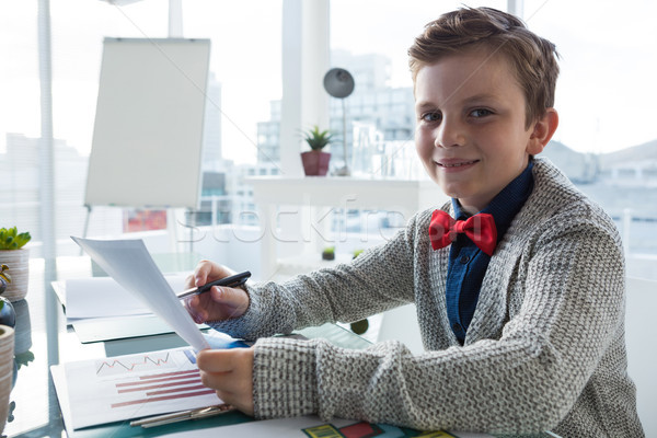 Boy as business executive holding document in office Stock photo © wavebreak_media
