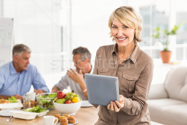 Smiling casual businesswoman using tablet at lunch Stock photo © wavebreak_media