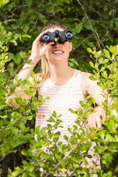 Smiling blonde looking through binoculars  Stock photo © wavebreak_media