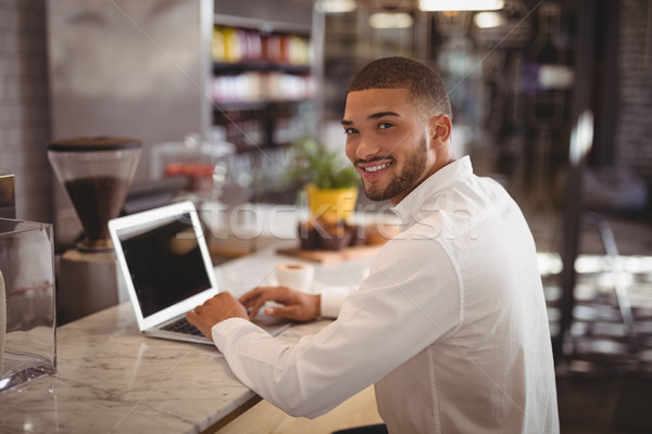 Portrait of smiling young male owner sitting with laptop at counter Stock photo © wavebreak_media