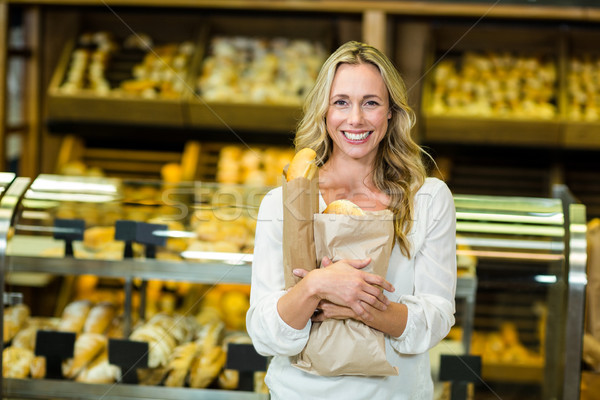 Beautiful woman holding paper bag with bread Stock photo © wavebreak_media