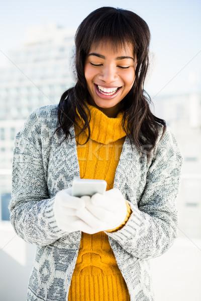 Mosolygó nő visel tél ruházat gépel telefon Stock fotó © wavebreak_media
