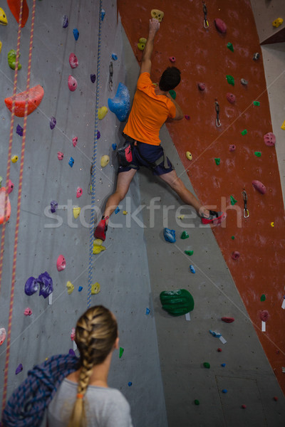 Woman with rope looking at man climbing wall in health club Stock photo © wavebreak_media