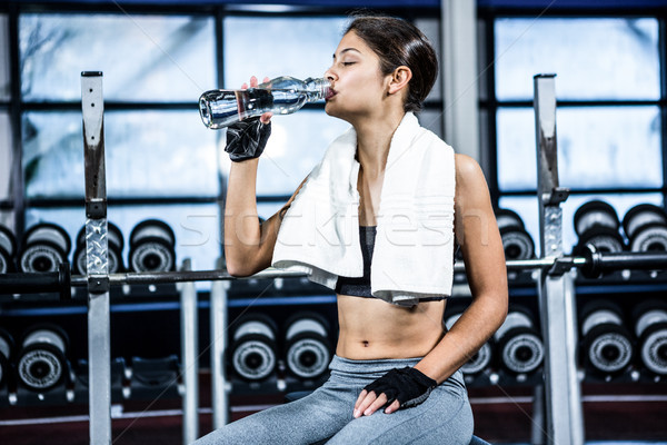 Muscular woman sitting on bench while drinking water Stock photo © wavebreak_media