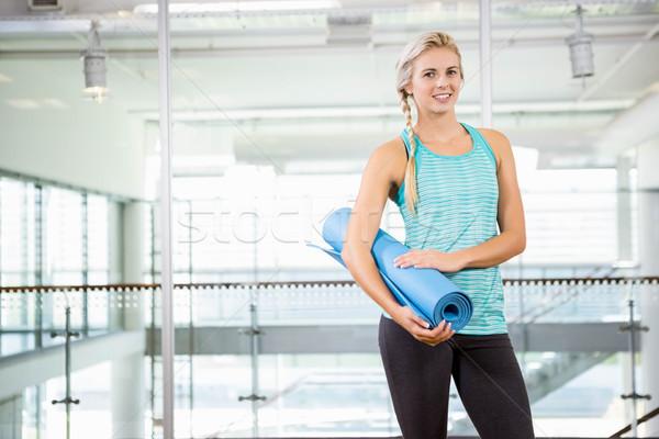 Smiling blonde holding yoga mat Stock photo © wavebreak_media
