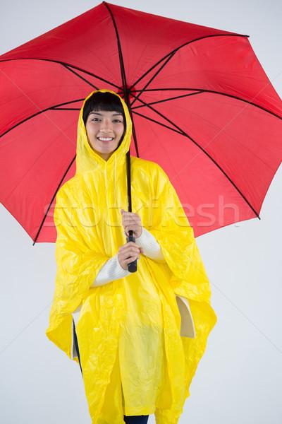 Nő citromsárga esőkabát tart esernyő mosolygó nő Stock fotó © wavebreak_media