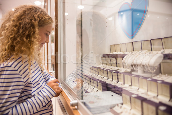 Happy girl looking at jewelry display Stock photo © wavebreak_media