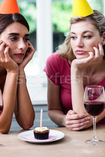 Sad friends sitting at table during birthday party Stock photo © wavebreak_media