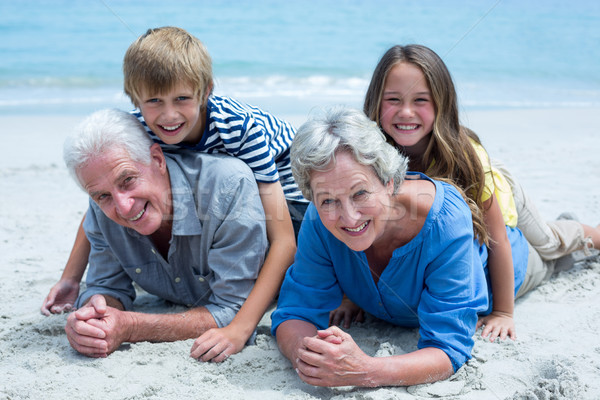 Children lying on grandparents at sea shore Stock photo © wavebreak_media