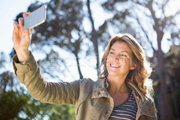 Smiling woman taking selfie Stock photo © wavebreak_media