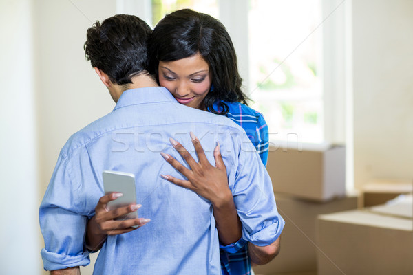Woman checking her mobile phone while embracing a man Stock photo © wavebreak_media