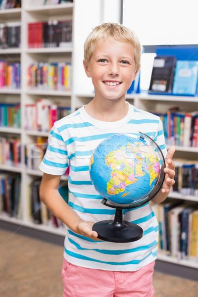 Schoolboy holding globe in library Stock photo © wavebreak_media