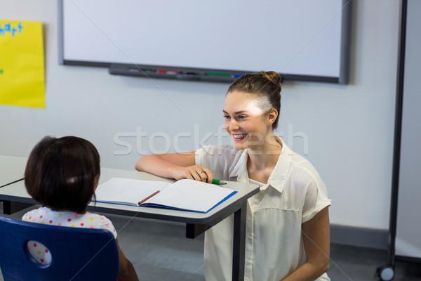 Female teacher kneeling by schoolgirl Stock photo © wavebreak_media