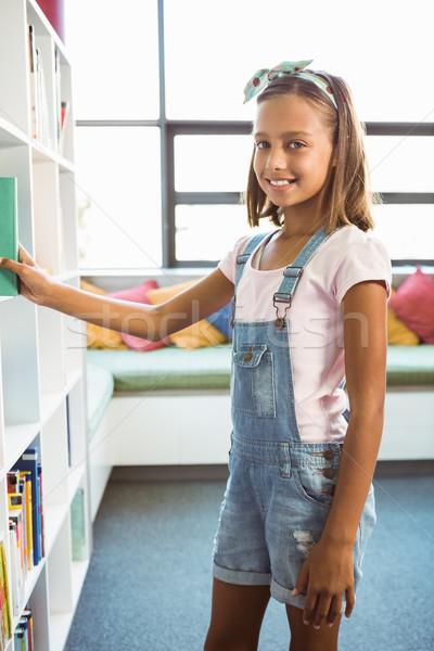 Girl taking a book from bookshelf in library Stock photo © wavebreak_media