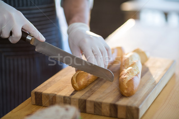 Waiter chopping bread roll on chopping board in café Stock photo © wavebreak_media