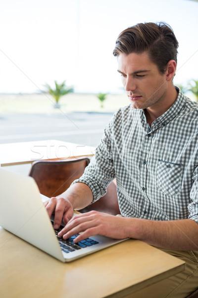 Stock photo: Man using laptop in coffee shop