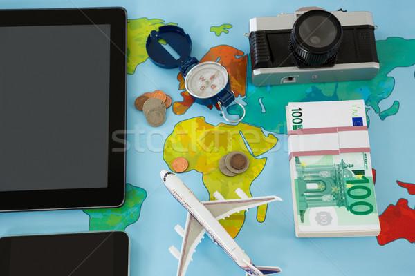 Electronic gadgets, camera, dollar, compass, and airplane model Stock photo © wavebreak_media