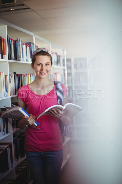 Portrait of happy schoolgirl holding book in library Stock photo © wavebreak_media