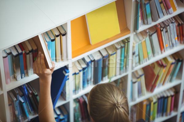 High angle view of schoolgirl selecting book from bookshelf in library Stock photo © wavebreak_media