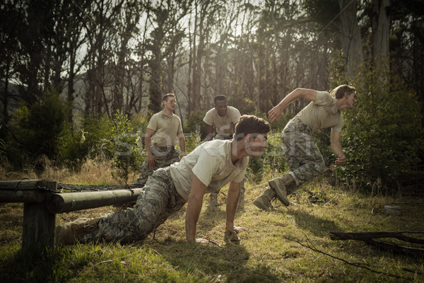 Soldiers crawling under the net during obstacle course Stock photo © wavebreak_media