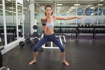 Smiling trainer standing in gym while women exercising in background Stock photo © wavebreak_media