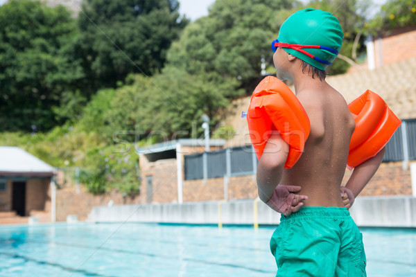 Boy wearing arm band standing at poolside Stock photo © wavebreak_media
