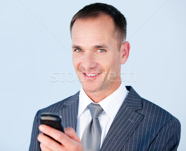 Confident businessman sending a text with his  phone  Stock photo © wavebreak_media