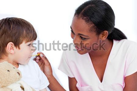 Stock photo: Smiling doctor taking child's temperature