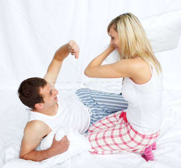 Amanti pillow fight camera da letto sorriso occhi capelli Foto d'archivio © wavebreak_media