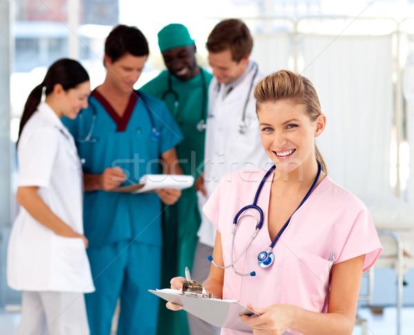 Blonde nurse with her team in the background Stock photo © wavebreak_media