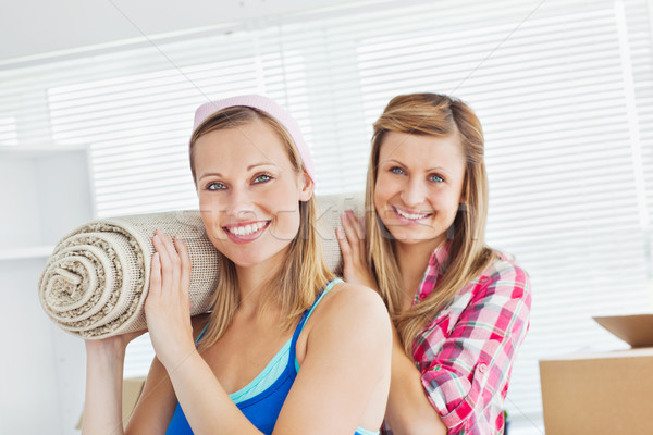 Two cute women carrying a carpet at home in their new location Stock photo © wavebreak_media