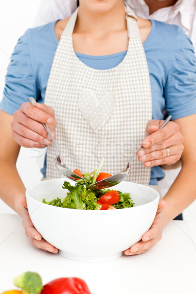 Close up of a couple mixing a salad together in the kitchen at home Stock photo © wavebreak_media