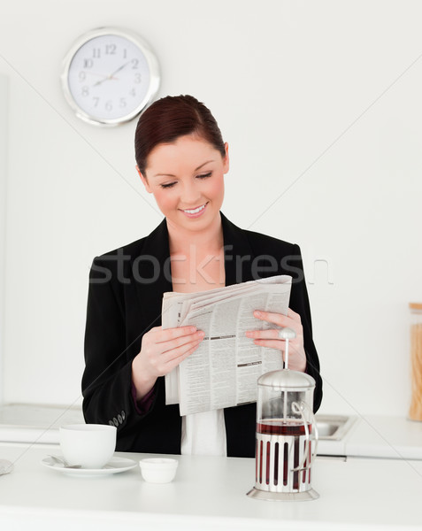 Good looking red-haired woman in suit reading the newspaper in the kitchen in her appartment Stock photo © wavebreak_media