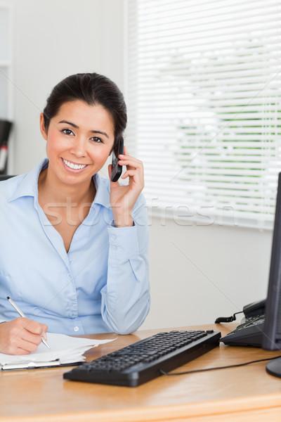 Atrakcyjna kobieta telefonu komórkowego piśmie arkusza papieru biuro Zdjęcia stock © wavebreak_media