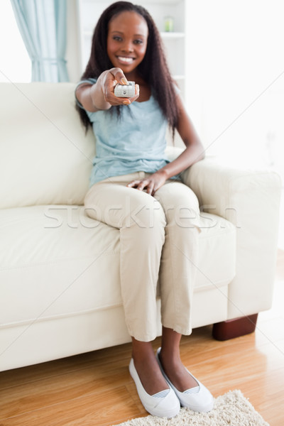 Smiling woman with remote control on sofa Stock photo © wavebreak_media